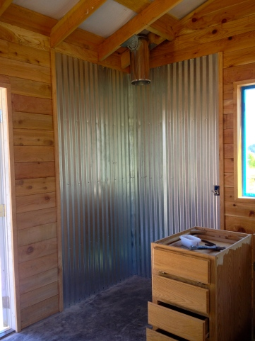Andrew installed some corrugated metal siding for insulation behind the wood burning stove