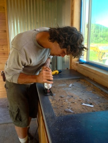 Andrew puts the finishing touches on the concrete counter top. The floors are also done...almost time to move in!
