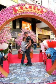 An arch with fake cherry blossoms was erected in honor of Chinese New Year. Andrew sports a short-lived mustache.
