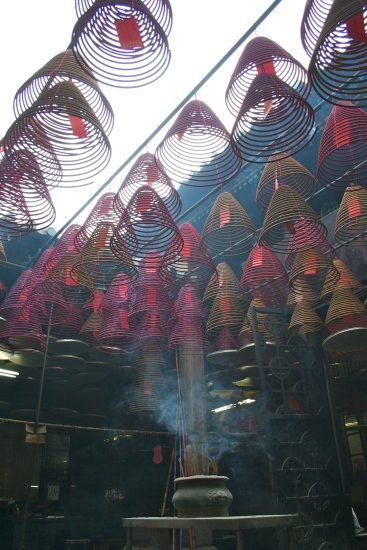 Giant incense coils burn in a quiet temple tucked between modern buildings on a busy street