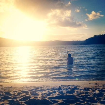 Andrew sits in the warm water as the sun rises over Lake McKenzie