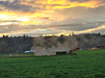 Andrew spreading steaming compost onto the fields at sunset